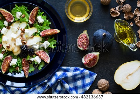 Salad with pears, lettuce, figs, walnuts, goat cheese, walnuts and honey on black background
