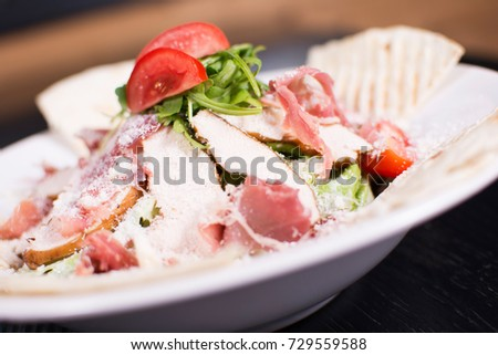 Salad with prosciutto and cheese on white plate close up. Served restaurant table. Delicious meal at a luxury restaurant.