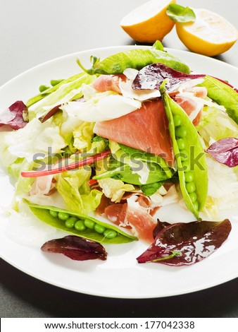 Salad with prosciutto, iceberg cabbage and green peas. Shallow dof. - stock photo
