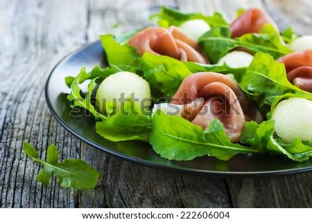 salad with prosciutto, melon and arugula, selective focus - stock photo