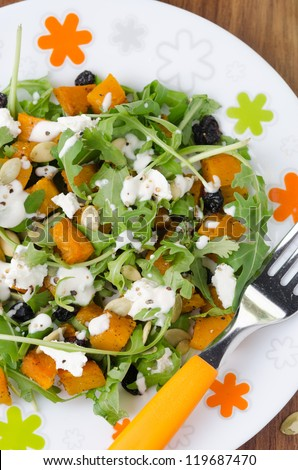 Salad with pumpkin, feta and arugula on a plate closeup view from above - stock photo