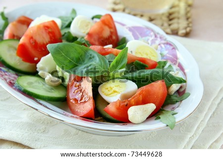 Salad with quail eggs and tomato on a plate