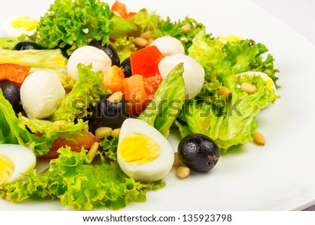 salad with quail eggs, pepper, olives, tomatoes and sesame seeds