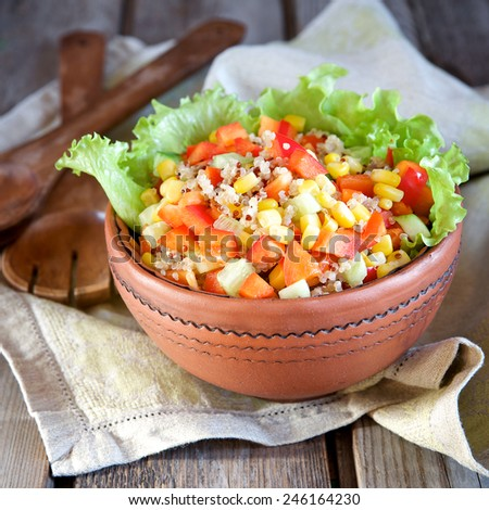 Salad with quinoa and vegetables in a ceramic bowl on a wooden background