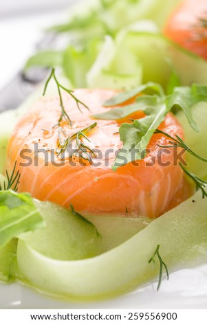 Salad with raw salmon and cucumber on white plate - stock photo