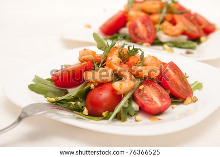 Salad with rucola, shrimps and cherry tomatos - stock photo
