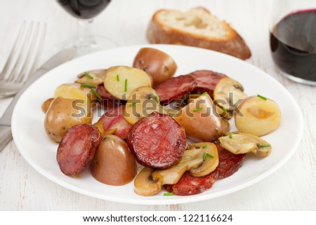 salad with sausages on the plate and glass of wine