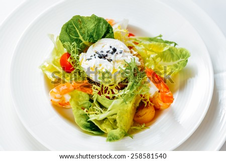Salad with shrimp and poached egg - stock photo
