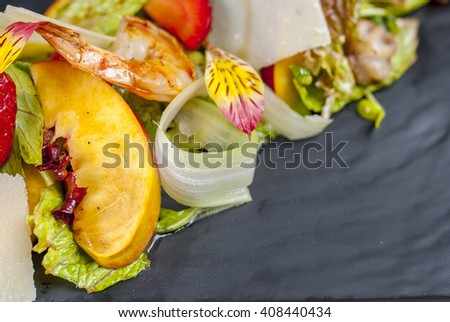 Salad with Shrimp's tails, octopus, squid, mussels and green fresh lettuce  peach strawberry on the white plate - stock photo