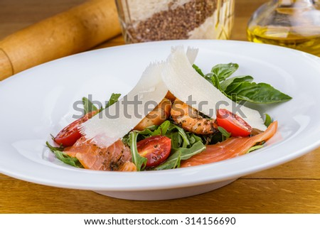 Salad with shrimp, salmon, arugula and cherry tomatoes