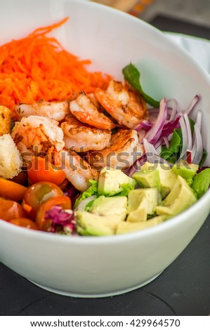 Salad with shrimps, octopus, mussels and calamari with avocado, lettuce, lemon and pineapple in a bowl, napkin on the background light wooden boards - stock photo