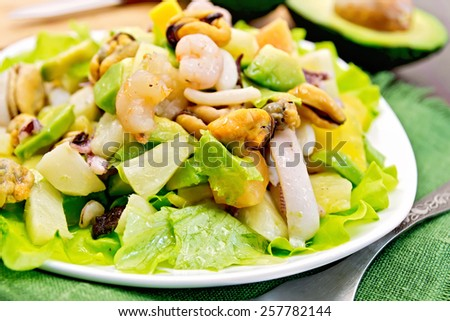 Salad with shrimps, octopus, mussels and calamari with avocado, lettuce, pineapple in plate on a green napkin, fork on the background dark wooden boards - stock photo
