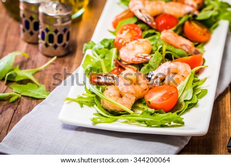 Salad with shrimps or prawn, tomato and arugula on wooden background