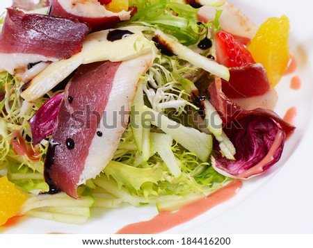 Salad with smoked duck breast close up