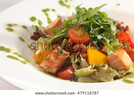 Salad with smoked salmon and vegetables and Arugula on plate