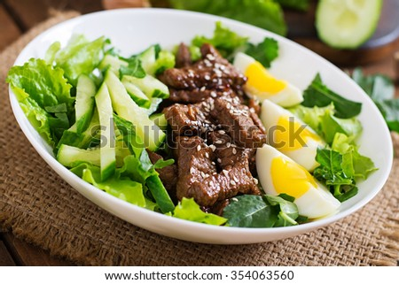 Salad with spicy beef, cucumber and eggs in the Asian style. - stock photo