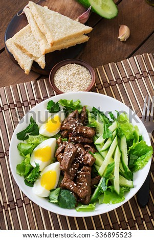 Salad with spicy beef, cucumber and eggs in the Asian style. Top view