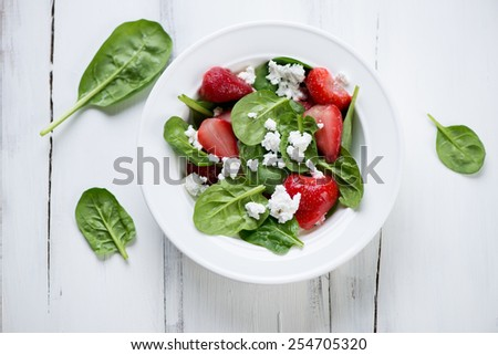 Salad with spinach leaves, strawberry and cheese, above view - stock photo