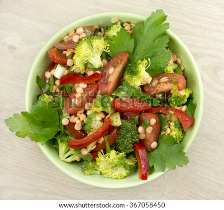 Salad with sprouts of red lentil, broccoli, tomato, sweet red pepper and parsley on a wooden background. Fully raw food. - stock photo