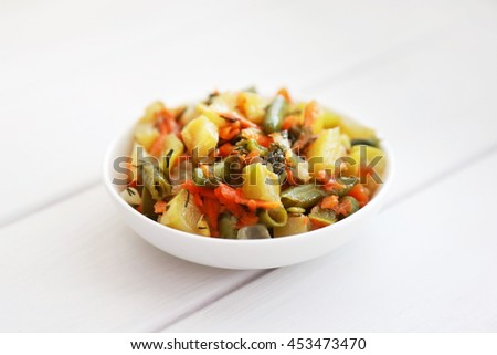 Salad with stewed vegetables (squash, carrot, french bean and dill) on ...