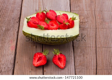 Salad with strawberries in melon over wooden background  - stock photo