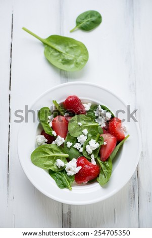 Salad with strawberries, spinach leaves and cheese, above view - stock photo