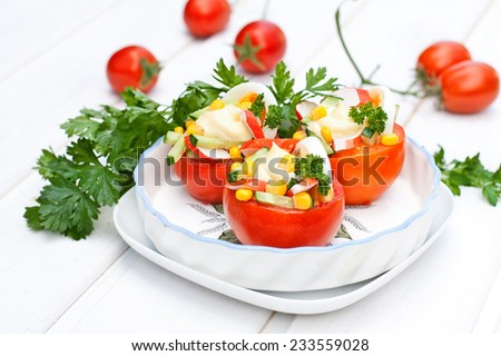 Salad with sweet corn and crab sticks, served in a tomatoes, on white background wooden table - stock photo