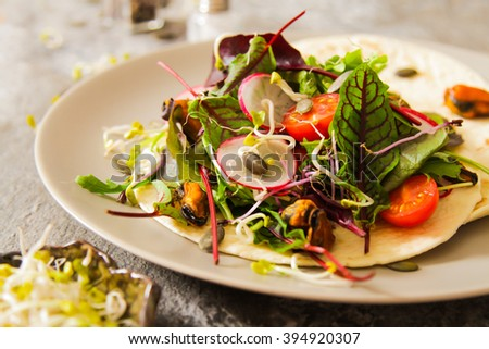 salad with tomato and radish sprouts for dinner on a wooden background