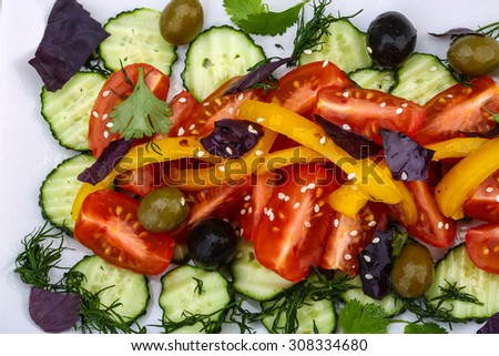 Salad with tomato, cucumber and olives served sesame seeds