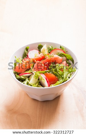 Salad with tomato, cucumber, radish, arugula and sesame seeds with olive oil