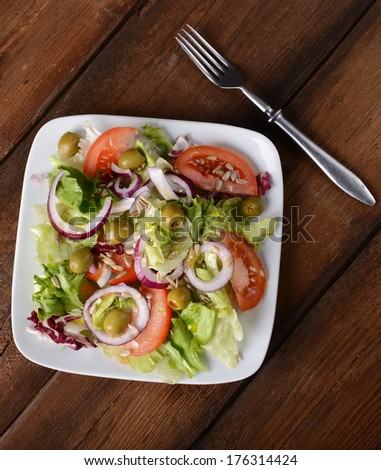 Salad with tomatoes and olives on wooden background