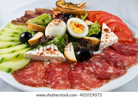 Salad with tomatoes, cucumbers, egg, cheese and sausage.