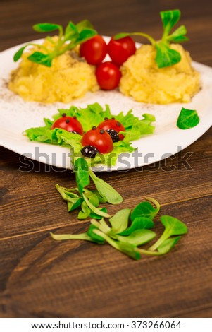 Salad with tomatoes decorated in the form of ladybugs with mashed potatoes - stock photo