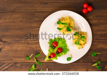 Salad with tomatoes decorated in the form of ladybugs with mashed potatoes. Top view - stock photo