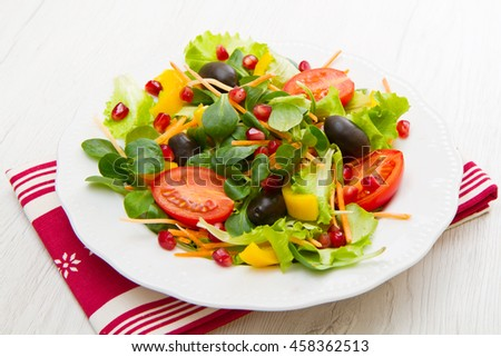salad with tomatoes in white plate on wood table
