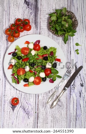 Salad with tomatoes, Mozzarella, olives, cabbage and ruccola and olive oil - stock photo