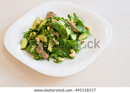 Salad with tuna and nuts on white plate