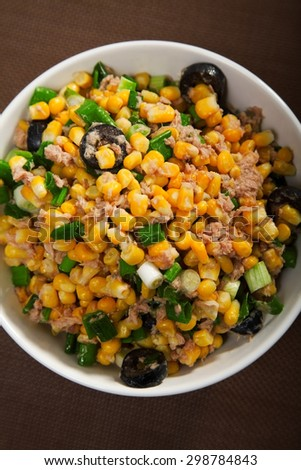 Salad with tuna fish, white corn, olives, green onions and olive oil in a salad bowl, shot from above