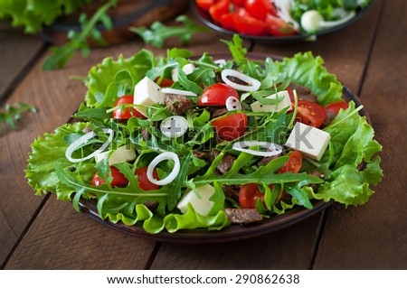 Salad with veal slices, arugula, tomatoes and feta cheese - stock photo