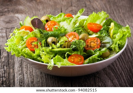 salad with vegetables and greens on wooden table - stock photo