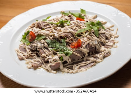 Salad with vegetables, meat on a  plate with tomatoes - stock photo