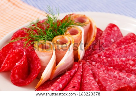 Salami and bacon on plate isolated on kitchen towels background.
