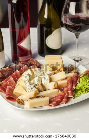 Salami catering platter with different meat and cheese products and different wines on the table - appetizer - stock photo