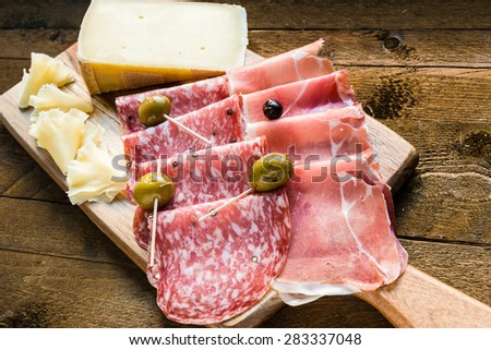 Salami, ham and cheese platter with olives. - stock photo