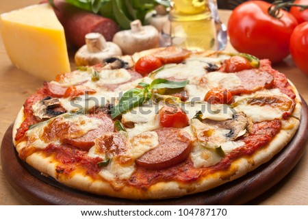 salami, mushroom and vegetable pizza with ingredients - stock photo