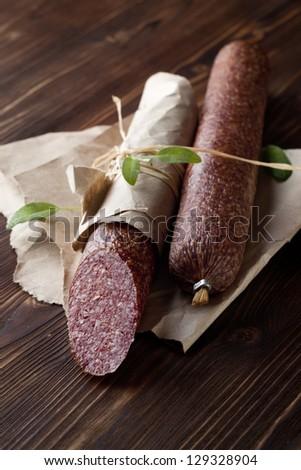 Salami on paper on dark wooden table - stock photo