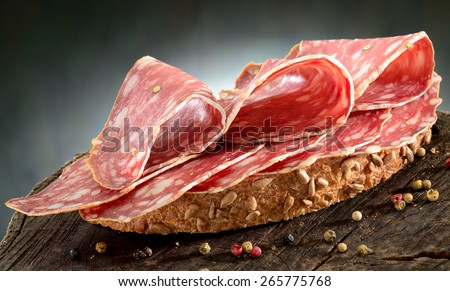 Salami sandwich. Open sandwich of salami slices on whole grain bread.  - stock photo