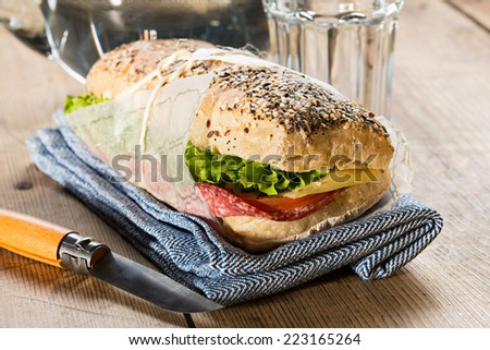 Salami sandwich with lettuce, cheese and tomato, placed on a blue cloth, with a wooden handle knife