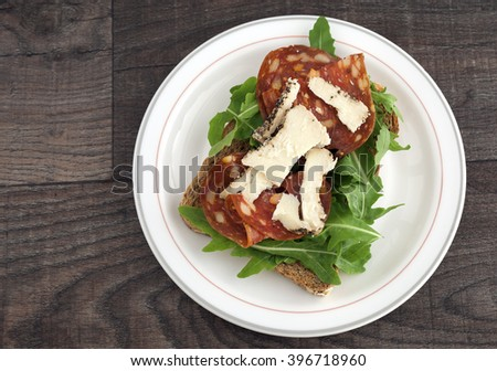 Salami sandwich with rucola, sheep cheese and brown bread.