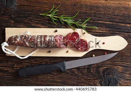 Salami sausages sliced, small cutting board and knife on old wooden table, top view
